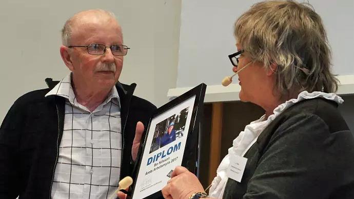 """Bo Nilsson tar emot priset """"Årets Arbetsmyra"""" av Arbetets museums vänförenings ordförande Li Teske."""