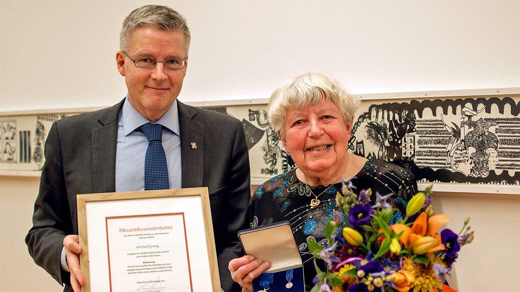 Gertrud Lyrung mottar förtjänstmedaljen 2017 från riksantikvarie Lars Amréus. Foto: Henrik Löwenhamn/Riksantikarieämbetet