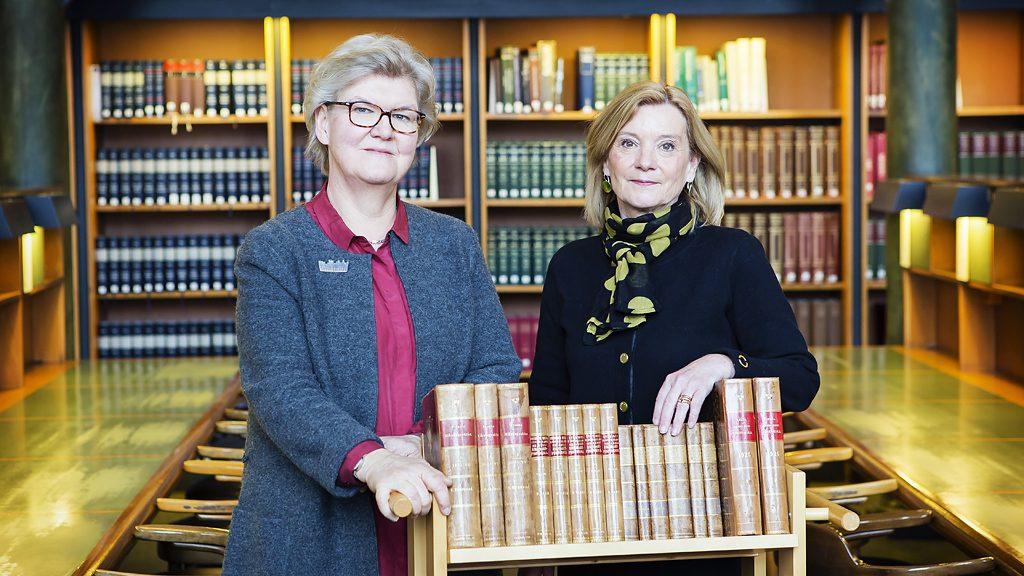 Riksbibliotekarie Gunilla Herdenberg och Kathrin Flossing, rikdagsdirektör vid Riksdagsförvaltningen med riksdagstryck i Kungliga bibliotekets stora läsesal. Foto: Caroline Tibell