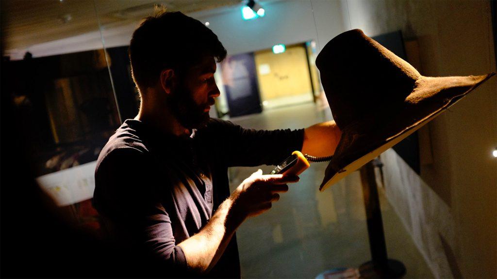 Museitekniker på Västerbottens museum mäter ljusstyrkan i en monter. Foto: Petter Engman