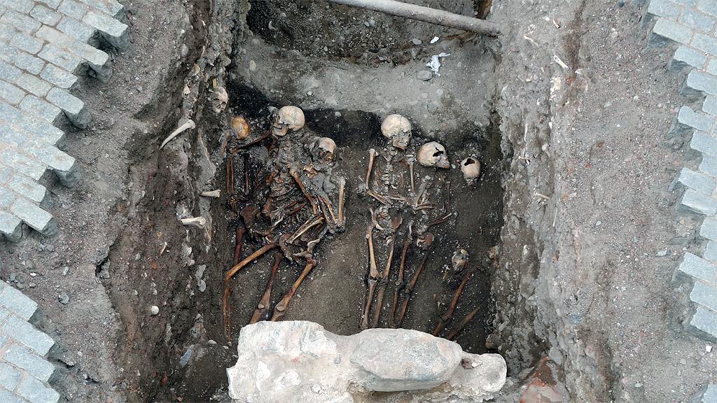 Äldre gravar och grupper av individer intill mur i väster. Foto: Arkeologikonsult AB