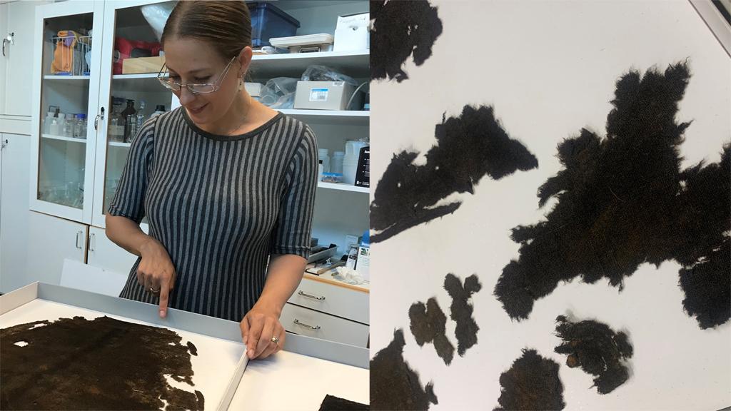 Anna Silwerulv visar dräktfynd från Vasa. Textilfragment. Foto: Catrin Rising/Vasamuseet
